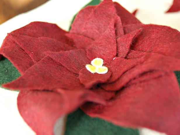 Apply fabric glue to the back of circles and stick them in a cluster to the center of each poinsettia. Allow fabric glue to fully dry before assembling pillow.