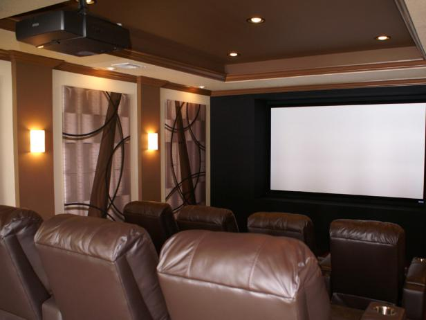 Once your drywall is painted, you can hang your speakers, projector, and screen. In a theater of 20 by 13 feet, the ideal screen size is 110-120 inches. For a professional feel, frame the screen with a proscenium – a set of black acoustic panels that hide the left, right, and center speakers.Camouflage the remaining speakers with acoustic panels that double as artwork. These panels can be printed with custom designs, including family photos or favorite movie posters.