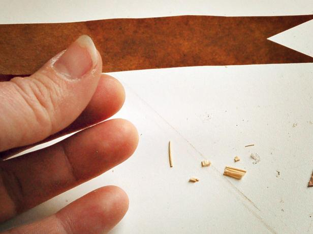 "Measure and cut a 3"" x 3/4"" pennant-shaped piece out of a brown paper bag and cut a small triangle out of right end."