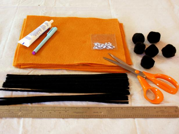 Supplies are laid out to make Halloween themed spider napkin rings.
