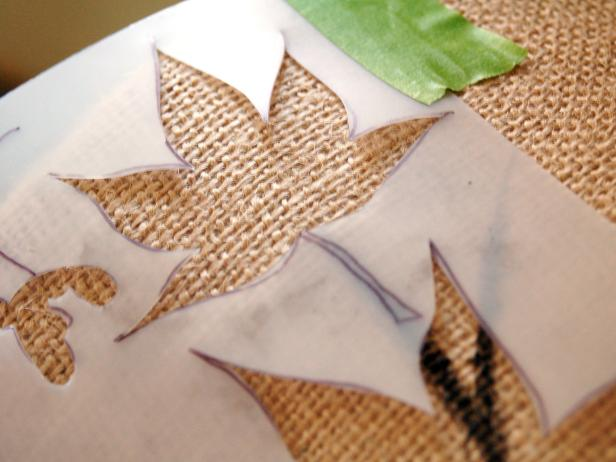 Secure leaf stencil to lampshade with painter's tape.