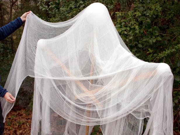 Gauze is draped on the frame of a DIY Halloween ghost for a spooky front yard decoration.