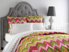 Gray Bed With Bold Pink and Green Patterned Bedding