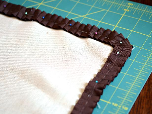 Position and pin pleated ribbon trim around perimeter pillow front.