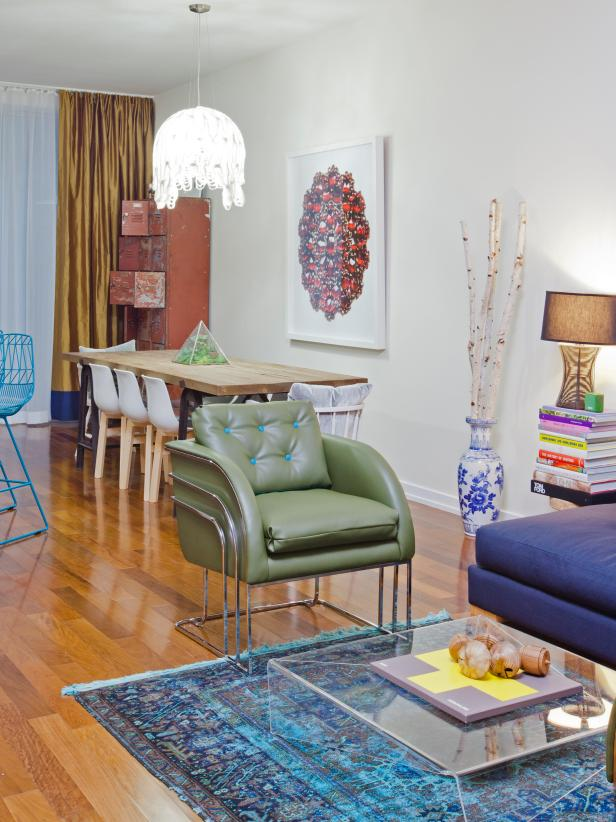 White Open Living Space With Green Chair, Blue Rug and Lucite Table