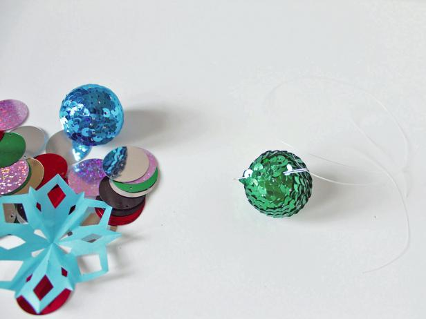 To create your holiday garland, string a 30-inch piece of monofilament onto the sewing needle. Start with the sequin ball by threading the monofilament through a top section of it.
