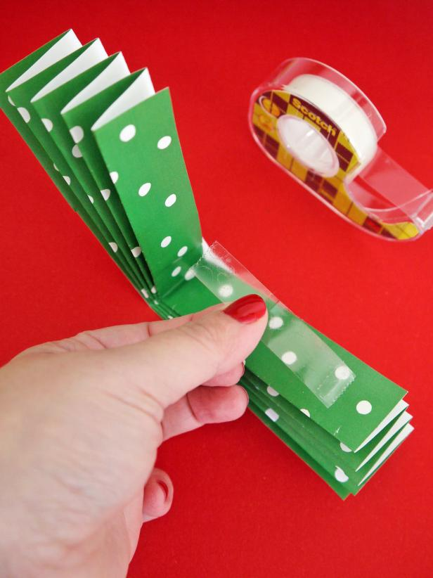 Fold each widthways and secure with tape. Attach all three pieces together and secure the middle with double-sided tape.