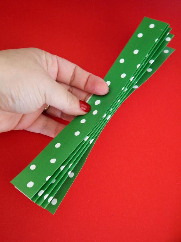 Fold a 8-1/2 by 11 inch piece of paper into an accordion with 1-inch folds. Repeat twice to get three folded rectangles of paper.