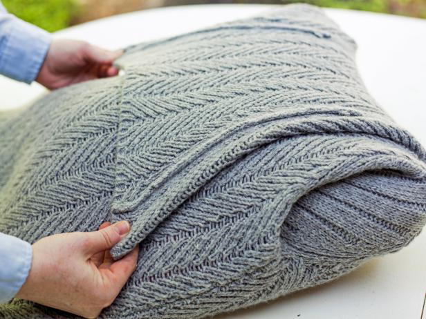 Folding the Neck of a Sweater Neatly Against a Pillow Form