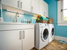 Vibrant Blue Laundry Room With White Cabinetry