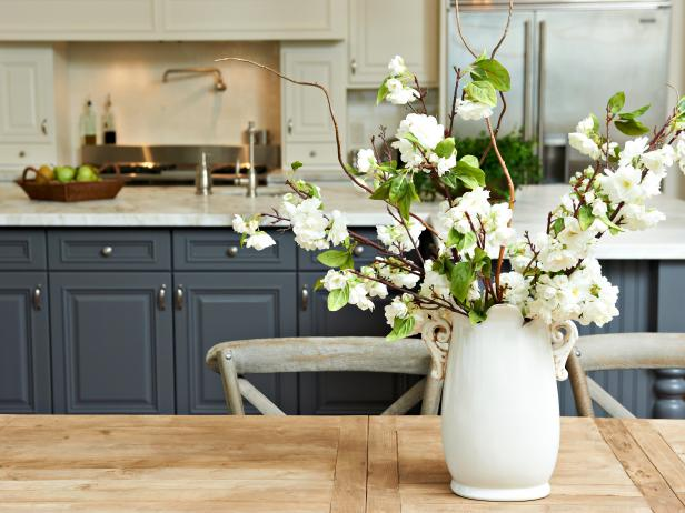 Kitchen With Pewter Blue Cabinets & Flowers in Vase on Wood Table