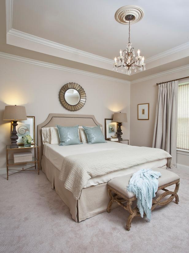 Transitional Neutral Bedroom With Cream Bedding and Chandelier