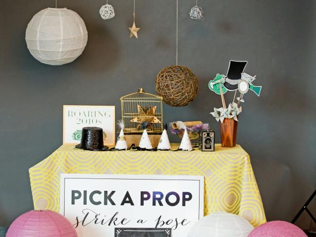 Assemble a prop station and display items guests can grab easily to pose with. A practical way to decorate the prop table without adding unnecessary items to the surface is to hang objects from the ceiling using twine and push pins. Make a simple signboard instructing guests to pick a prop and strike a pose and place it near the prop table.