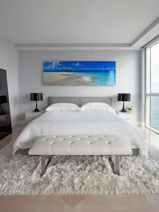 White Contemporary Bedroom With Large Beach Photograph and Black Lamps
