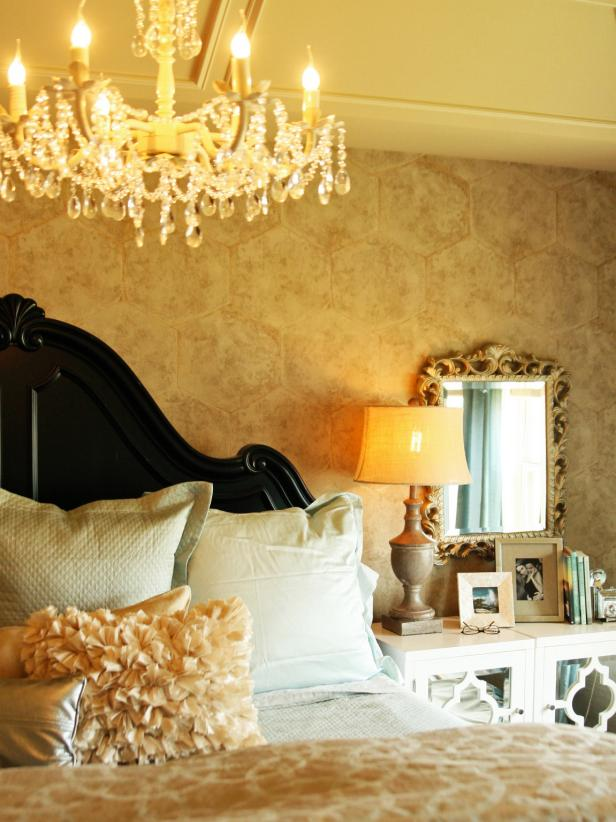 Master Bedroom With Gold Wallpaper and Grand Chandelier
