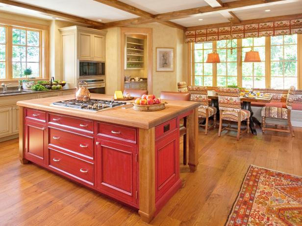 Yellow Country Kitchen With Beamed Ceiling and Red Island