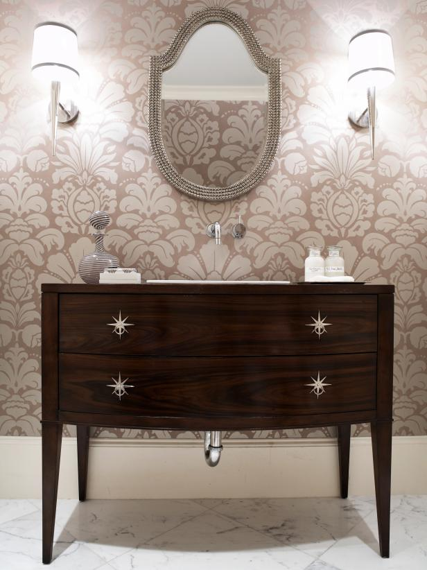 Powder Room With Pale Pink Patterned Wallpaper and Wood Vanity