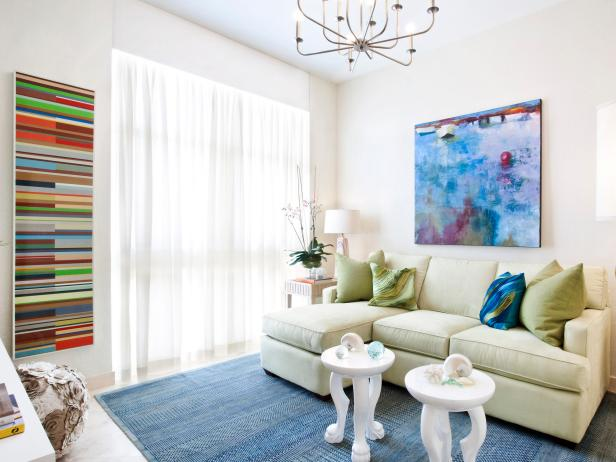White Living Room With an Extended Sofa and Colorful Artwork