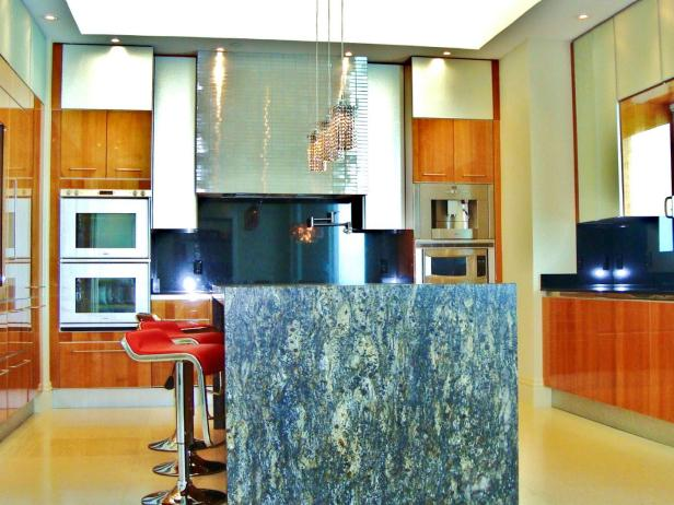 Streamlined Kitchen With Aluminum Range Hood and Granite Island