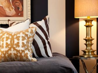 Guest Bedroom With Neutral and Gold Pillows and a Bronze Lamp