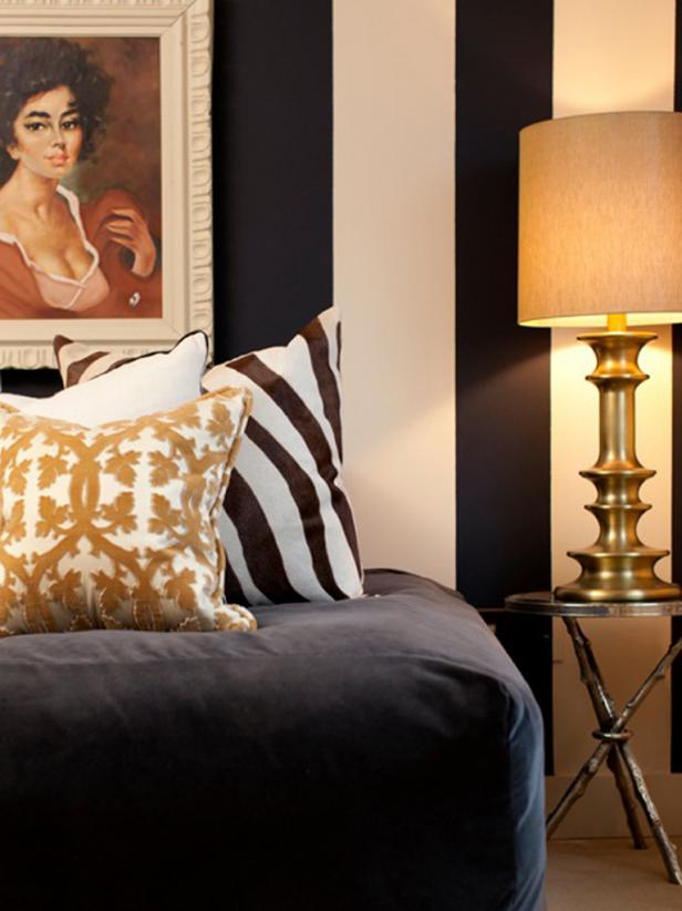 Guest Bedroom With Neutral Pillows, Bronze Lamp and Striped Walls