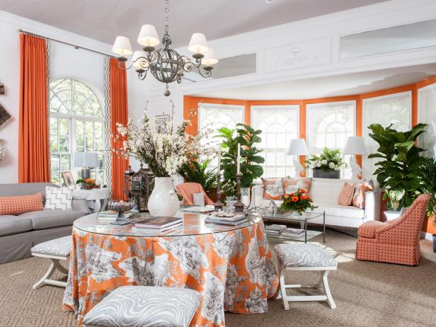 Orange and White Sunroom With Toile Skirted Table and Stools