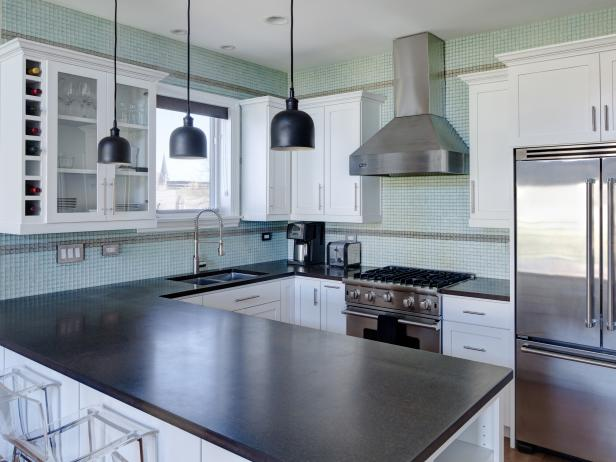 Kitchen With Blue Tile Backsplash, Black Countertop and White Cabinets