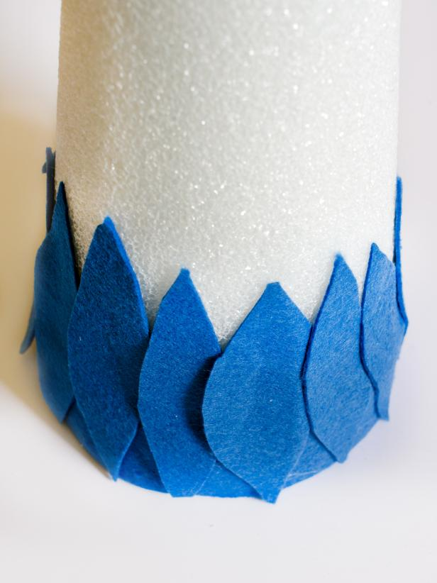 Apply hot glue in small sections around the base of each tree form and immediately press strip of darkest felt in place. Just above felt strip, apply a bead of hot glue vertically and immediately press the darkest felt feather into glue. Hold in place for few seconds until glue cools. Repeat with other dark felt feathers, placing them side by side so they slightly overlap, concealing the cone. Once the entire bottom row is finished, start a second row of dark felt feathers just above first row. Continue to glue feathers on, graduating from dark to light in rows of two. Tip: Use a moderate amount of hot glue. You don't want glue to squeeze out when felt feathers are pressed down.