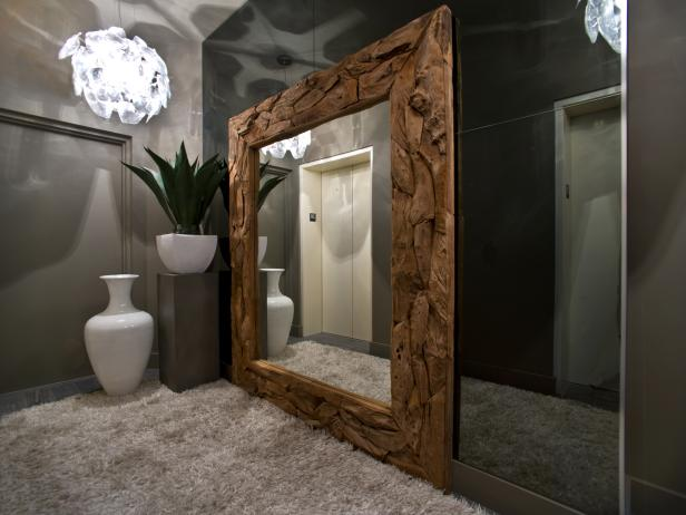 Driftwood-Framed Mirror Reflecting Elevator Doors in Neutral Foyer