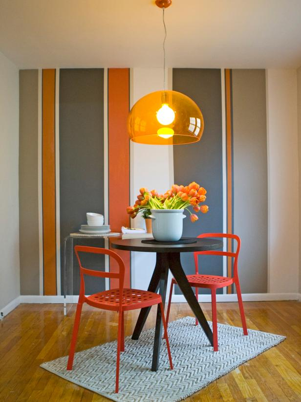 Dining Room With Striped Accent Wall & Shades of Orange