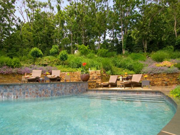 Outdoor Pool With Stacked Stone Retaining Wall and Lounge Chairs
