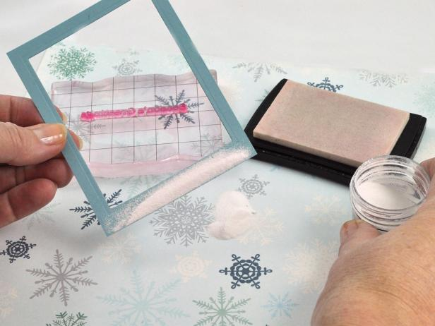 Tap off excess embossing powder from the frame of the snow shaker holiday card.