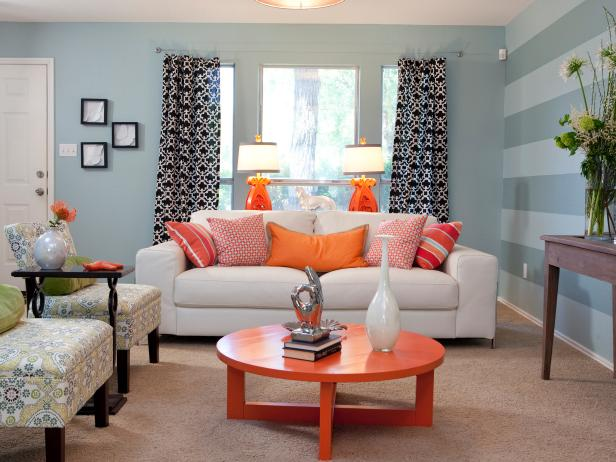 Blue transitional living room with orange accents light blue walls