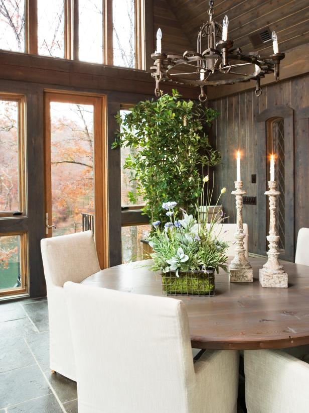 Rustic Dining Area With Round Wood Table and Iron Chandelier