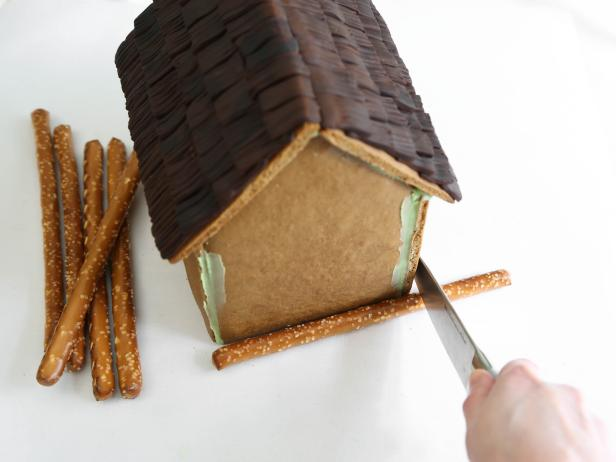 Measure pretzel rods against the front of the house and cut to size with a sharp knife.