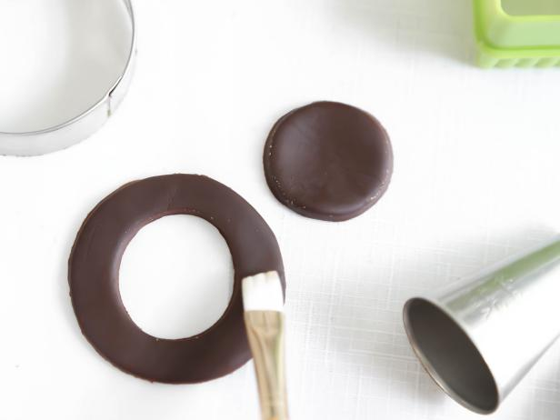 Cut a 3-inch round piece of chocolate fondant, and then cut out a 1 1/2-inch circle from the center using the large end of a piping tip or a bottle cap to begin creating the wreath for your gingerbread house.