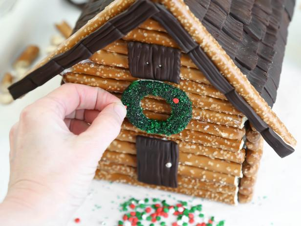 For an adorable finishing touch on a log cabin-style gingerbread house, adhere a chocolate fondant wreath just above the front door using royal icing. Press in confetti sprinkles onto wreath.