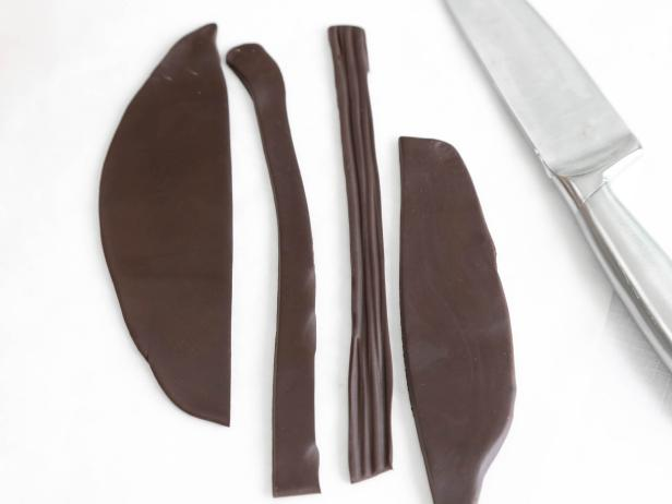 Cut long strips of chocolate fondant in matching lengths and striate with a toothpick or the back of a knife to begin forming the edge of the roof.