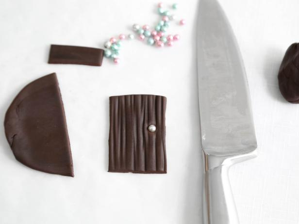 Cut a 2 1/2 x 1 1/4 piece of chocolate fondant that has been rolled to 1/4-inch thickness, and serrate with a toothpick or the back of a knife. This will be the front door to your gingerbread house.