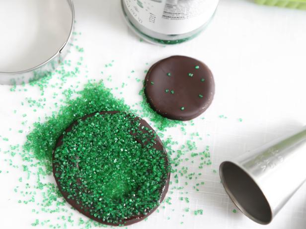 Lightly coat the chocolate fondant circle with water and sprinkle over green sanding sugar. Let set until partially dry.