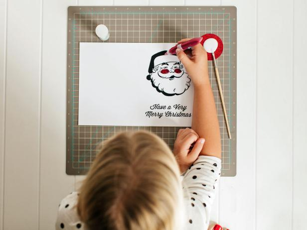 "Use glitter glue, cotton balls, markers or any other fun embellishments to make your Santa card truly one-of-a-kind. Tip: For the ""Dear Santa"" card design, have the kids write to Santa or create a wish list inside the card."