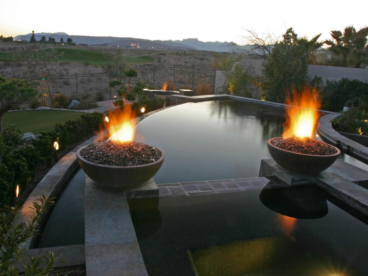 Crescent shaped pool with fire features hgtv - Pool fire bowls ...