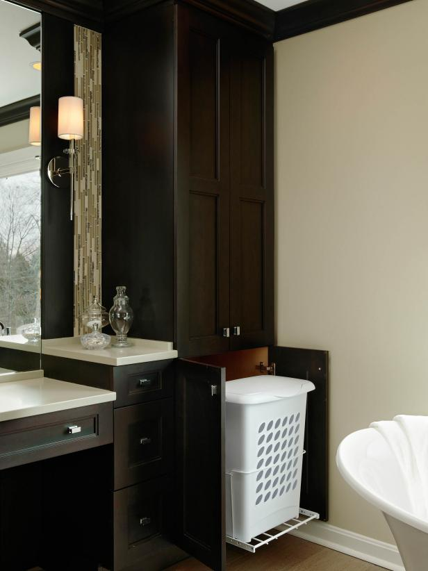 Dark Cabinetry With Hamper Pullout in Neutral Bathroom