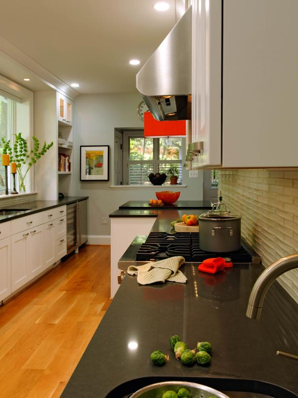 Contemporary Kitchen With White Cabinets, Black Quartz Counters and Red Accents