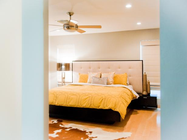 Sleek Neutral Bedroom With Yellow Bedding and Cowhide Area Rug
