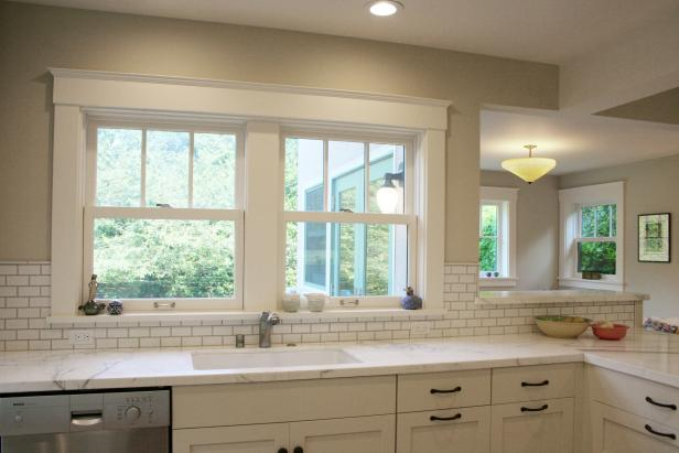 Neutral Kitchen With Marble Countertops and Subway-Tile Backsplash
