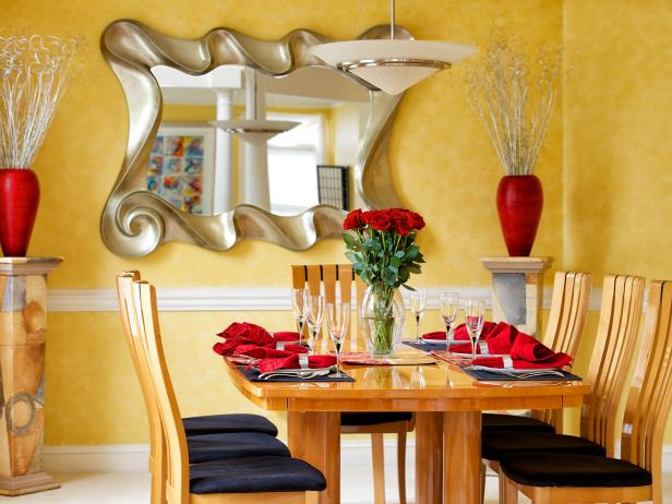 Dining Area With Yellow Walls and Contemporary Mirror