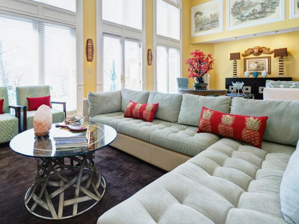 Sage Green Sectional With Red Pillows and Glass Coffee Table