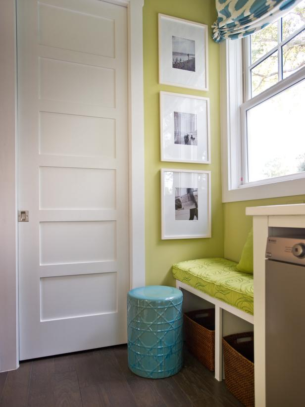 Contemporary laundry room in green and white, with built-in bench.