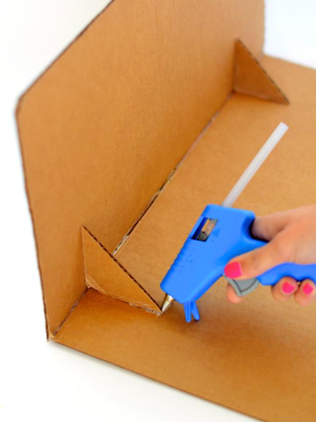 Use hot glue gun to create a right angle out of two cut cardboard flaps. Once dry, glue cut cardboard corners into inner corner of right angle as pictured.